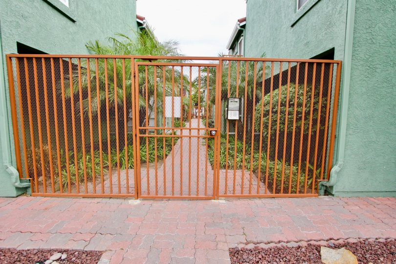 Iron railing gate narrow path landscaped in Majestic Palm.