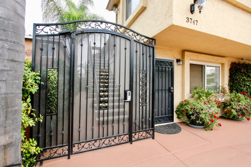 A number keypad sits on a black gate at North Park Villas