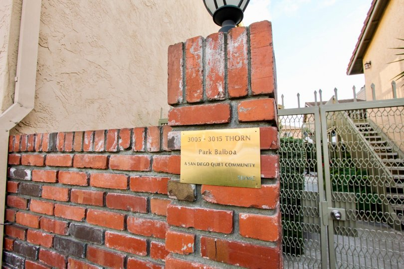 In brick wall, A board mentioned as A san Diego quiet Community 3005-3015 thron