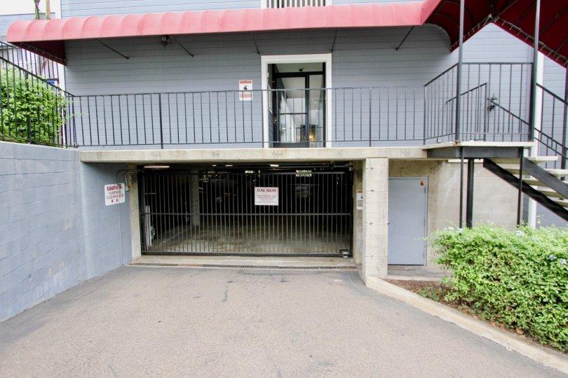 Blue brick garage entrance in Parkside with trimmed hedges and a gate