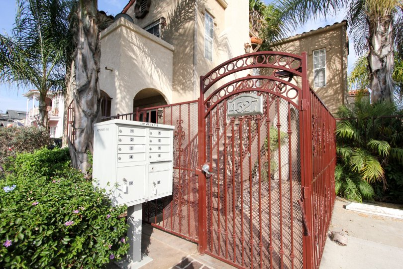 Beautiful iron gate sourrounded by plants and trees at Swift Park in North Park, California.