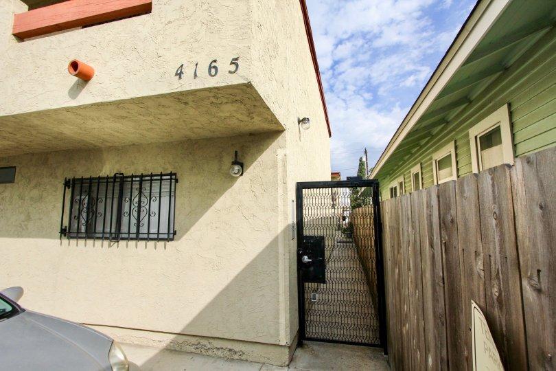 Looking between buildings down a narrow alleyway through a black gate in Villa de 33rd in North Park, California