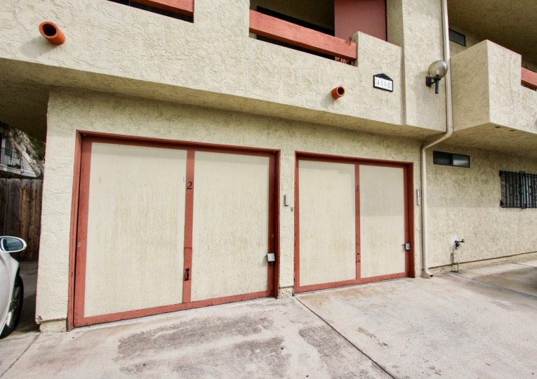 The exterior of Villa De 33rd shows 2 garage doors and two parking spaces below balconies