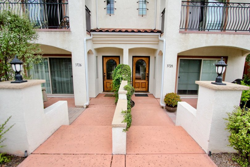 Two wooden doors with glass at their centers inside Villas De Mediterraneo in North Park CA
