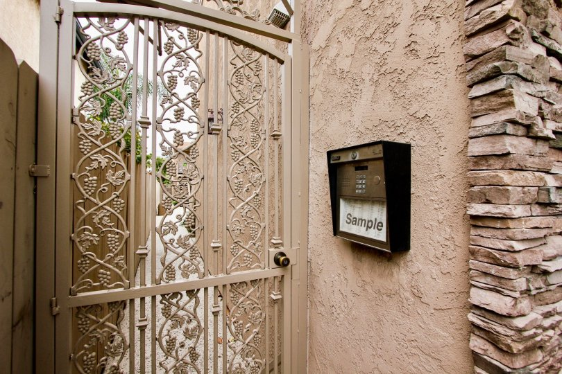 Metal intercom at pink gate inside Villas on Idaho at North Park CA