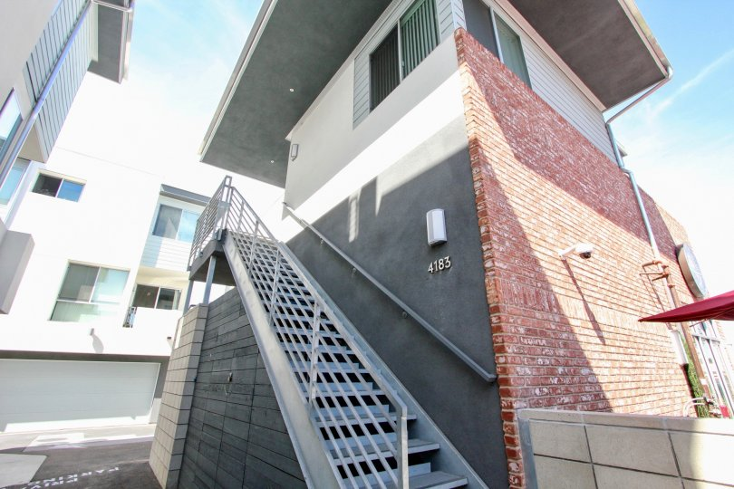Contemporary styling with exterior brick feature wall and horizontal iron railings at Famosa Townhomes