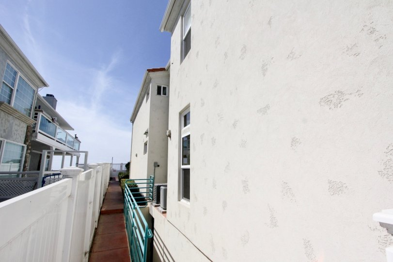 A narrow passage between white houses in Ocean Front Condos