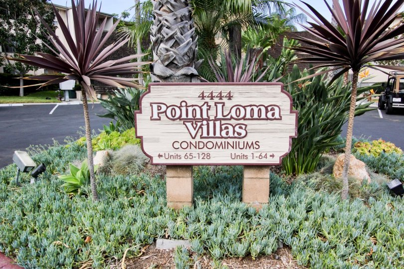 The Sign of Point Loma Villas Condominium with a small garden and a jeep in the backgroound