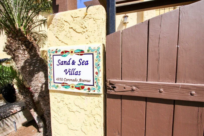 "A red, white, yellow and blue sign reads ""Sand and Sea Villas"""