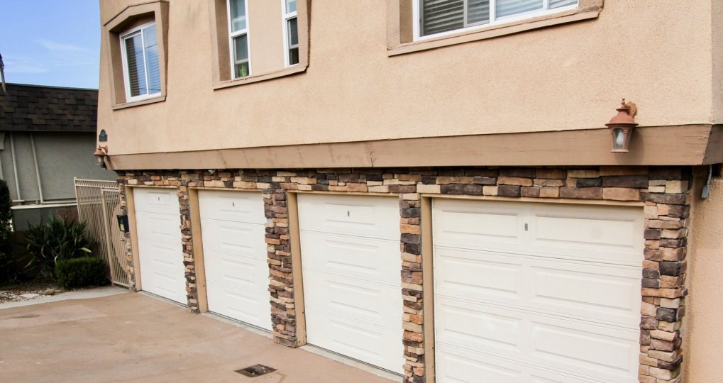 A tan and brown stone surround is seen around white garage doors at Temecula Heights