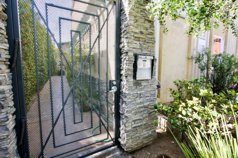 A sunny day at The Beach House, in front of the community gate with an intercom system and near a garden.