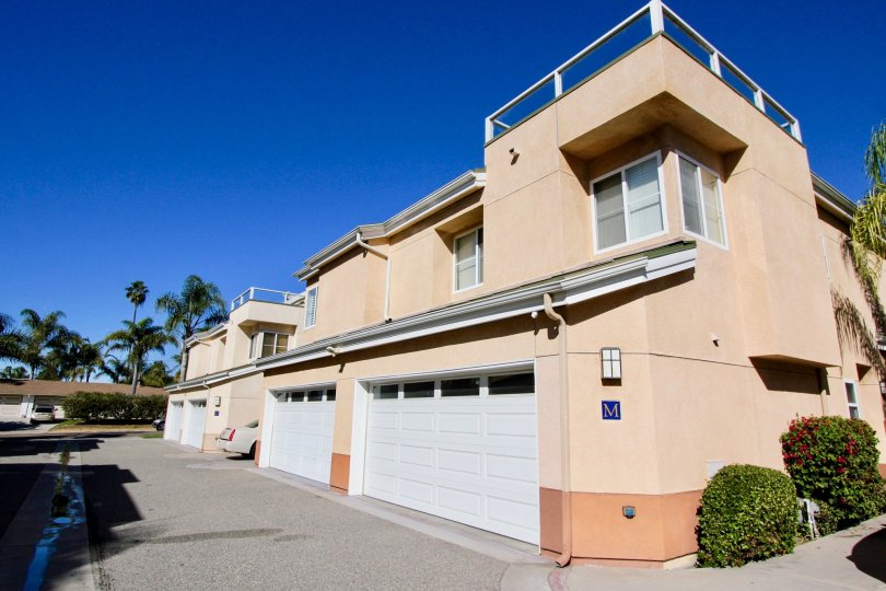 Four garages with white doors built into Eaton Court in Oceanside CA