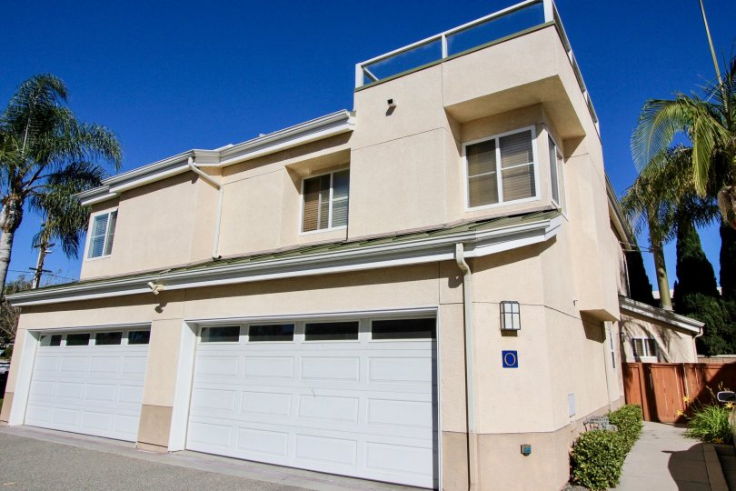 External view of double garage doors and two-story building at Eaton Court in Oceanside, California