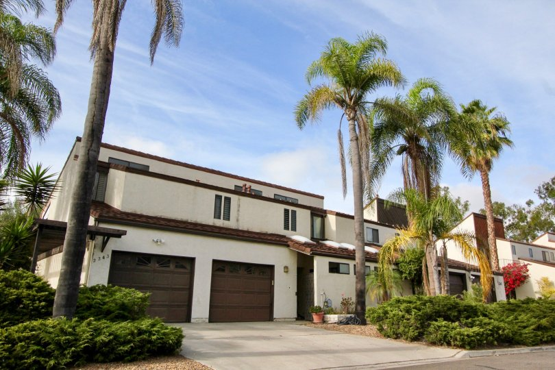 An El Camino Villa residential building with palm trees and garages in Oceanside California