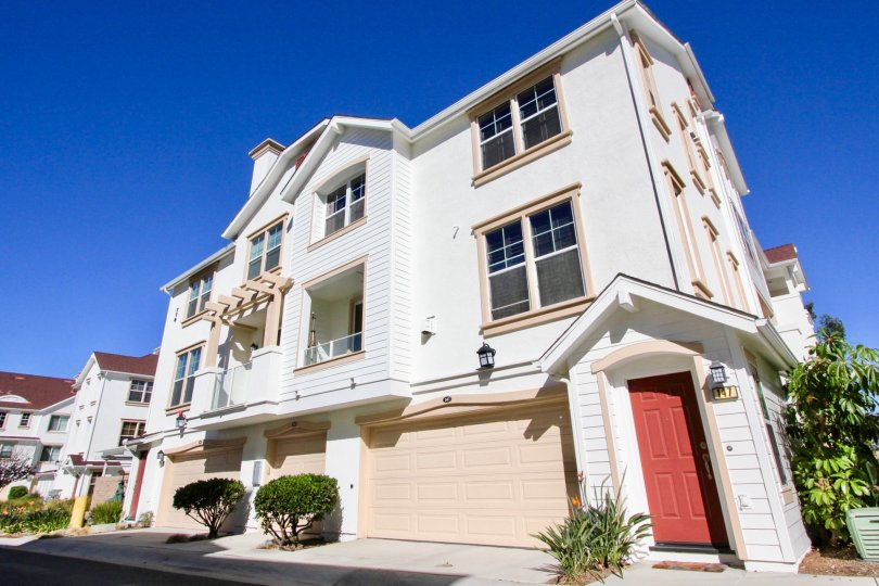 The outside of a unit at the Harbor Cliff condominiums with private entrance, garage, and balcony under a blue sky.
