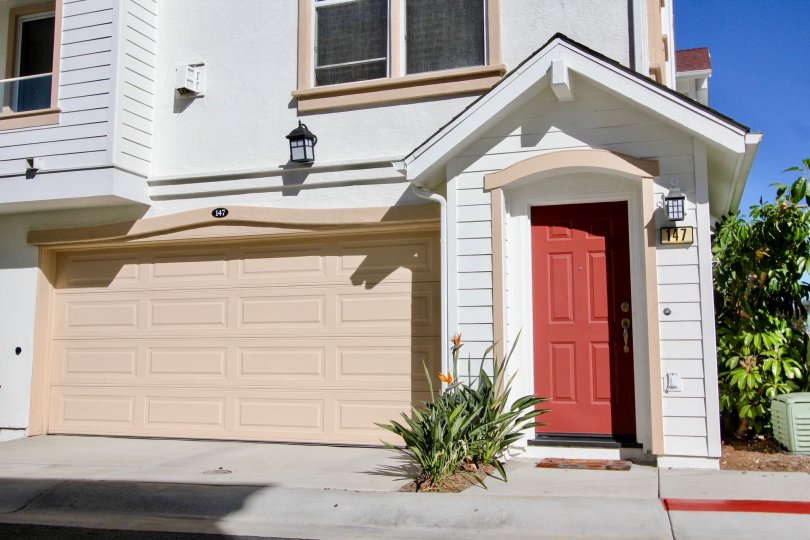A house has a red door and a pink garage in the Harbor Cliff community in Oceanside, California.