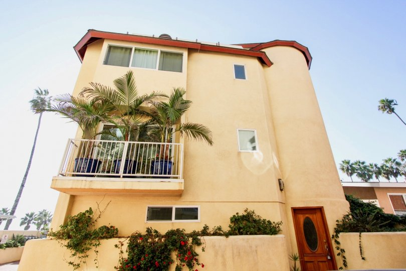 A tall stucco apartment building in Hibiscus area community of Oceanside CA.