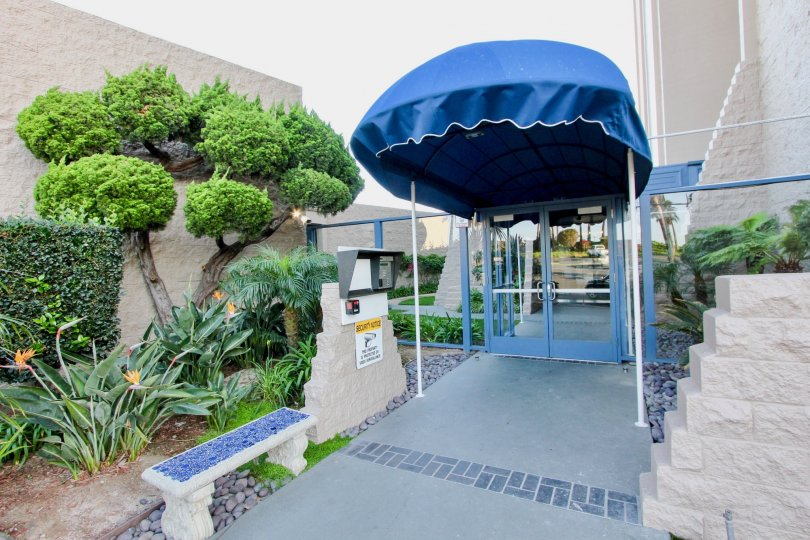 Walkway with a blue canopy near buildings at Marina Towers in Oceanside CA