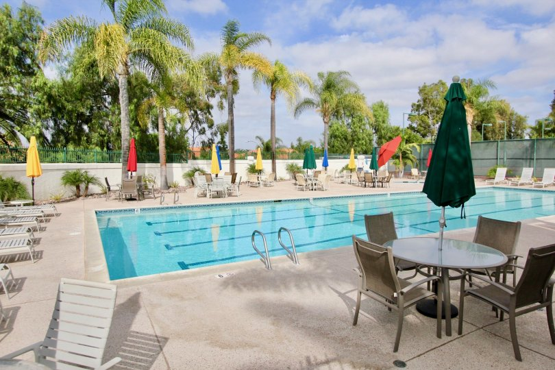 Pool view with colorful poolside umbrellas and loungers at Mission Point Townhomes in Oceanside, California