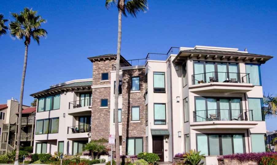 Three story building with brick and glass walls at Montego Condominiums in Oceanside CA