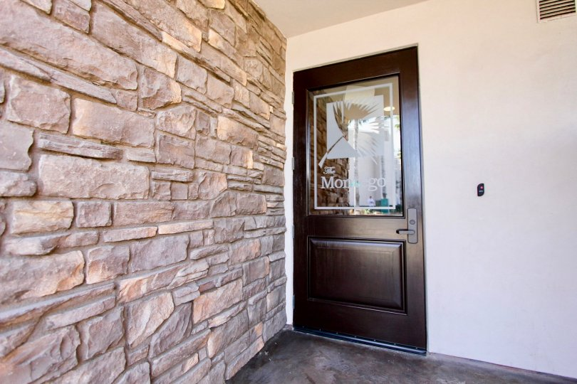 A stone wall by a door leading to the office of Montego Condominiums in Oceanside, CA