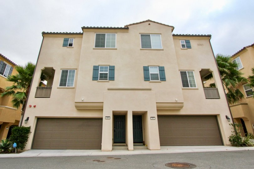 A duplex with garages and trees at North River Village in Oceanside, CA
