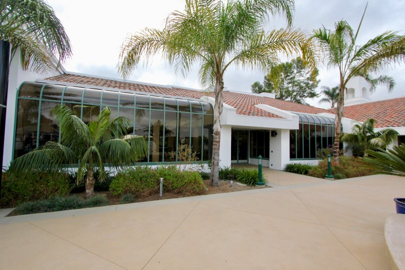 In the Ocean Hills Country Club communtity a small building has palm trees in front.
