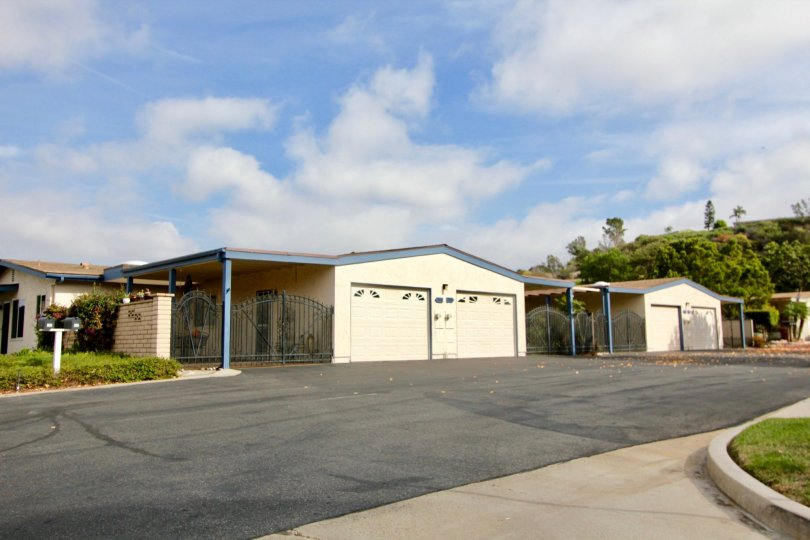 An exterior view of the Oceana Mission homes with garage and private gated carports from the street.