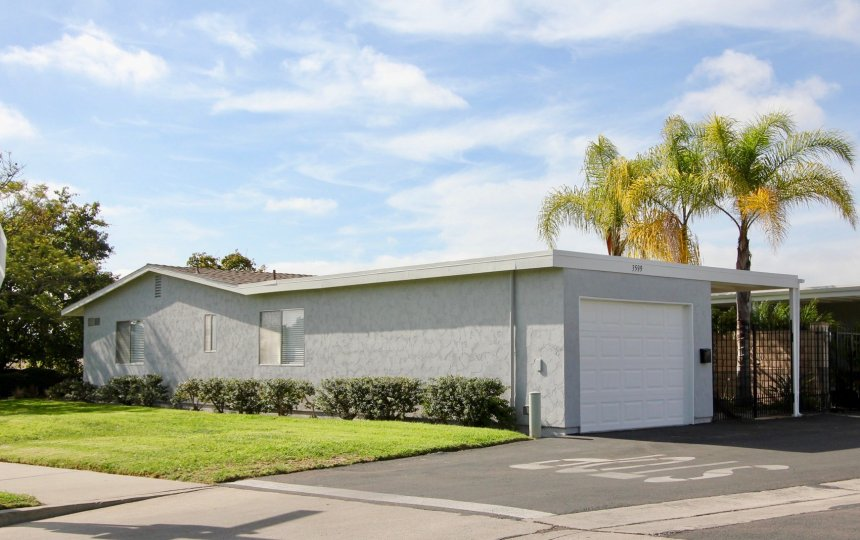 Single story long gray home with yard & attached garage inside Oceana south in Oceanside CA