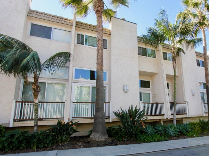 Pink two story home with windows and railings lined with palms inside Ovard in Oceanside CA