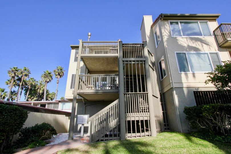 An exterior view of the Pacific Star Pine apartment homes showing the community mailbox, exterior staircase, and balconies.