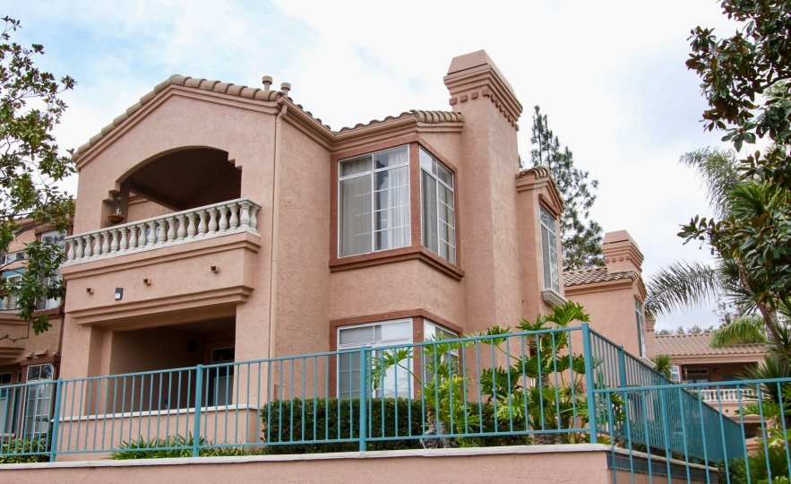 Large two story red stone apartments with large windows and fenced in lawns atPalmilla Del Oro