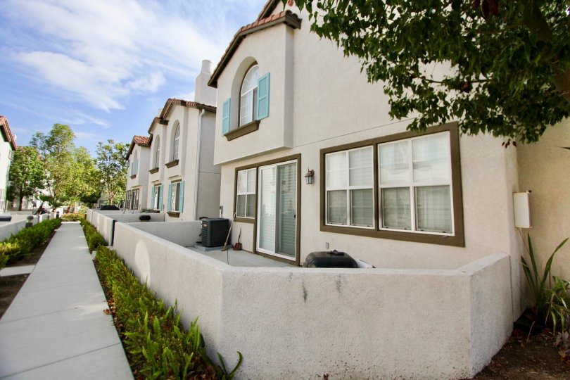 Two story housing behind a white wall & sidewalk in Pelican Cove in Oceanside CA