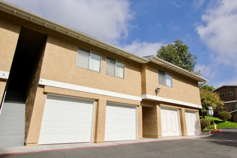 Two story brown condos with white garage doors inside Quail Ridge in Oceanside CA