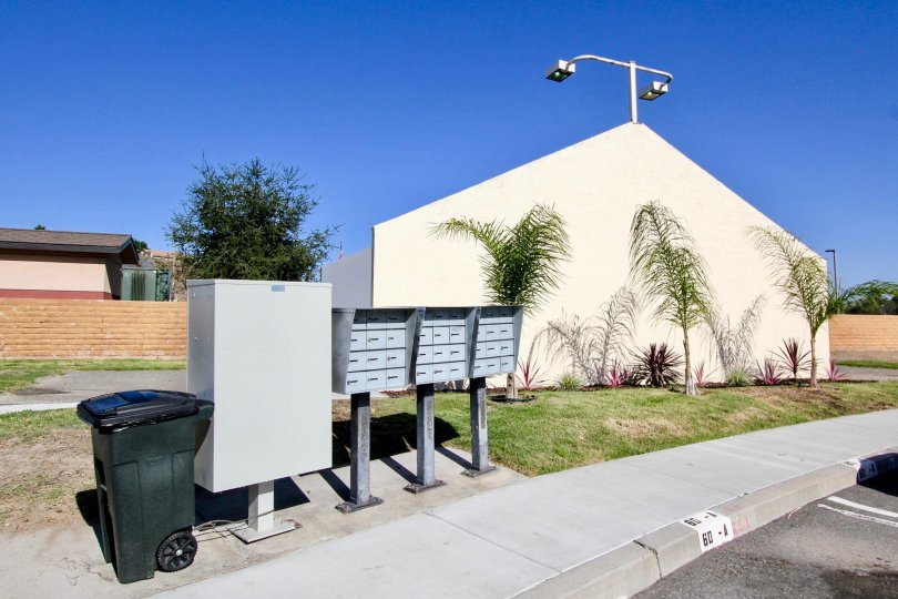 Metal mailboxes next to a trash can in Oceanside CA at Riverview Townhomes