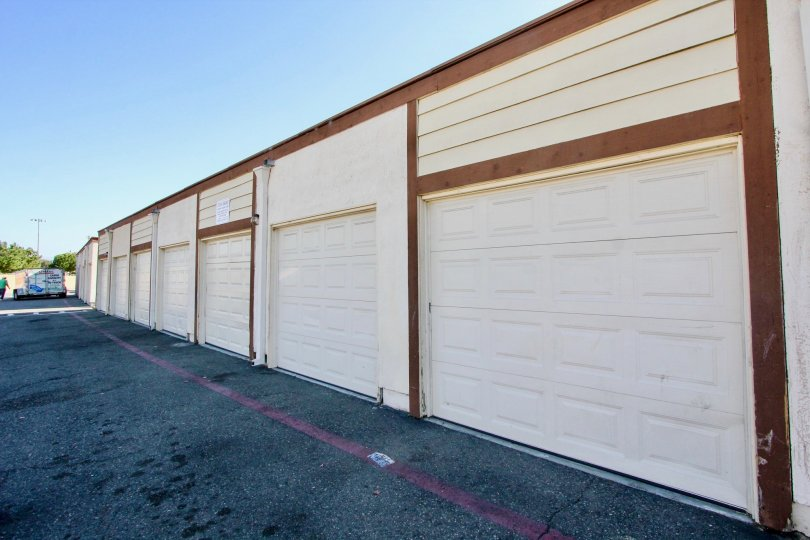 Brown and white garages lined up next to a street at Riverview Townhomes in Oceanside CA