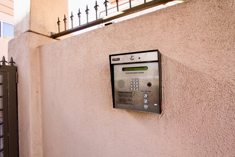 A callbox sits on a tan wall outside the San Miguel III condos