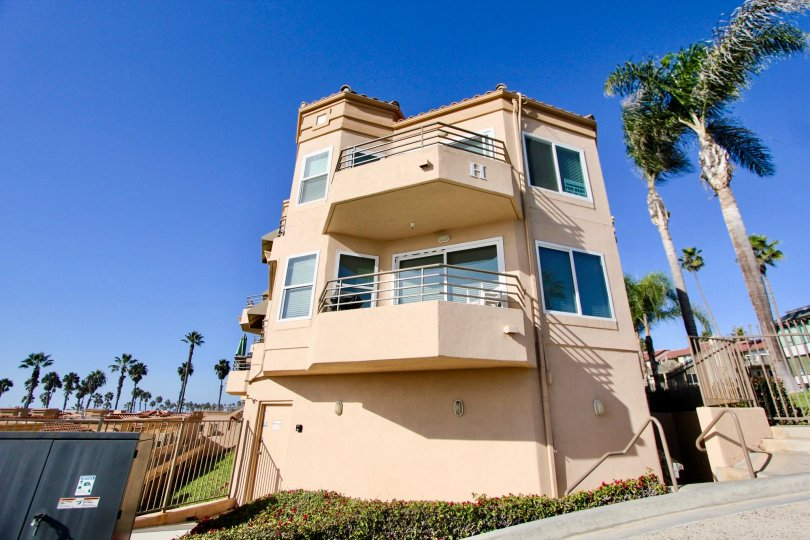Sunny day overlooking large three story house with tan walls and 2 balconies.