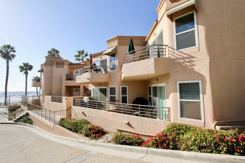 Two story pink homes lined with plants near the ocean at San Miguel III in Oceanside CA