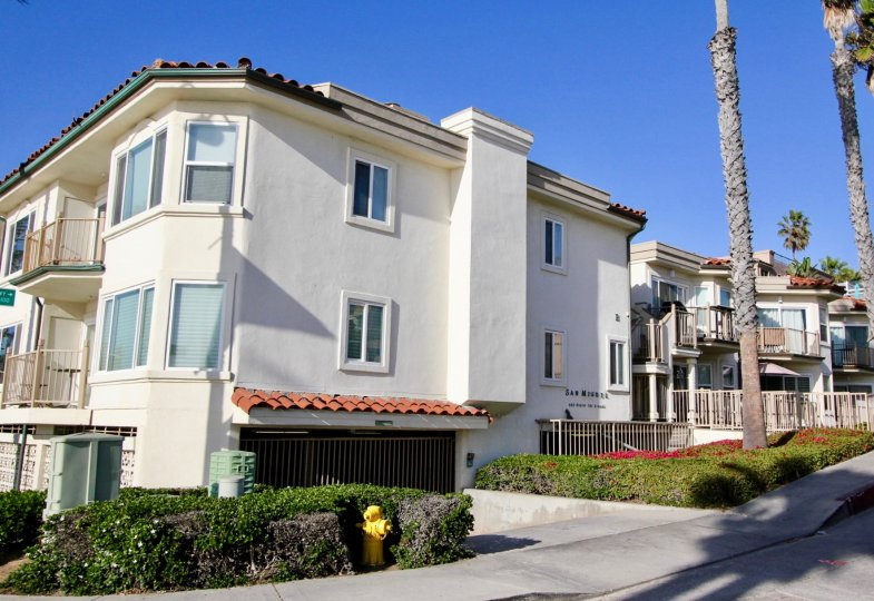 Condominium complex with gated parking and professional landscaping with palm trees in San Miguel, Oceanside, CA