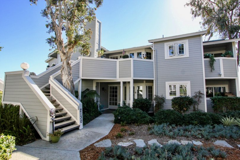 Gray two story building with a rock walkway garden inside Sandpiper Cove in Oceanside CA