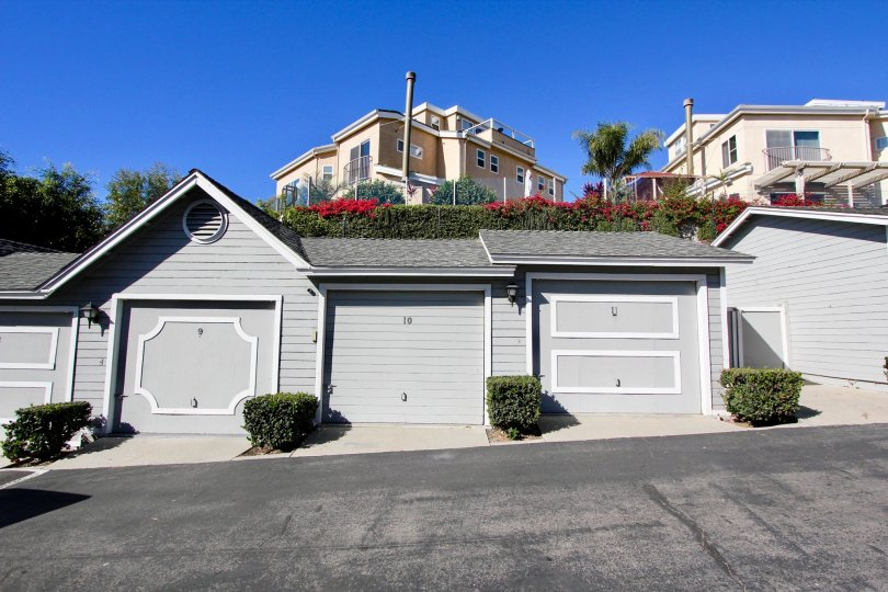 Attached vinyl-sided attached garages on a backlane in the community of Sandpiper Cove, Oceanside, CA