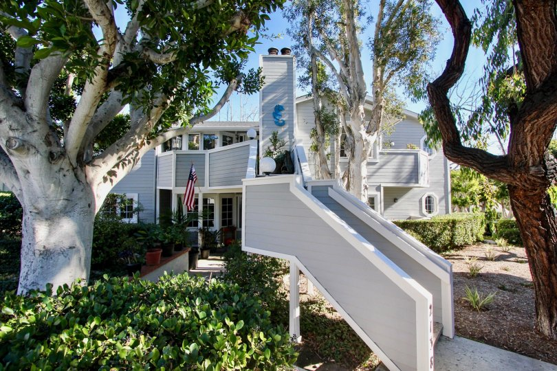 THE BUILDING IN THE SANDPIPER COVE WITH THE UPSTAIRS, TREES, FLAG, WINDOWS, FLOWER WASH