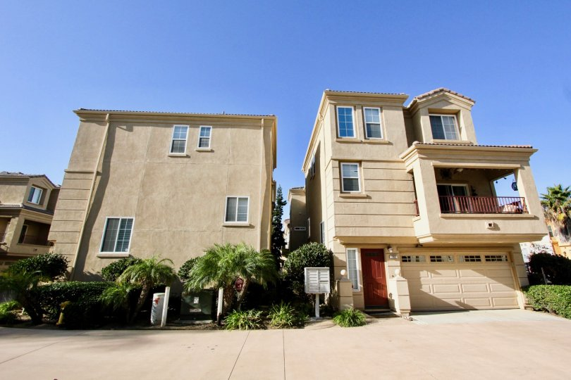 Three story town homes with a large brown garage door next to plants inside Sea Breeze Beach Cottages in Oceanside CA