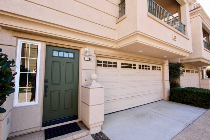 Green front door, balcony and gargage door of 713 Sea Breeze Beach Cottages in Oceanside, CA.