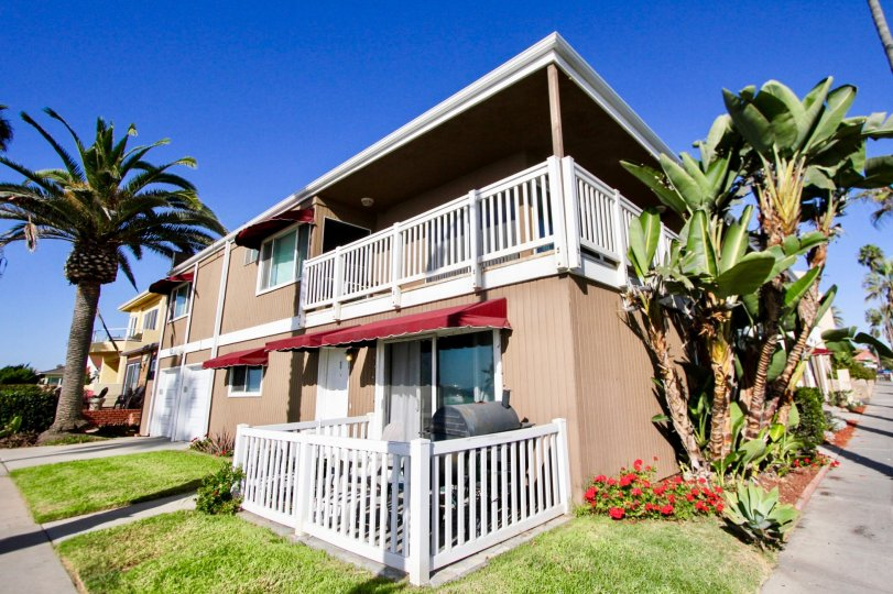 Two story wooden building with white rails in Oceanside CA at Sea Spray Villas II