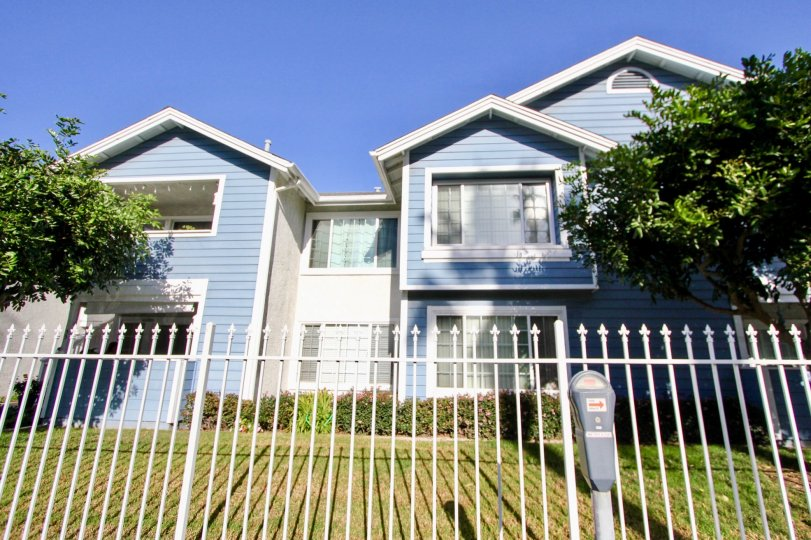 Light blue, two-story house with white fence in the community of Sea Village, located in Oceanside, California