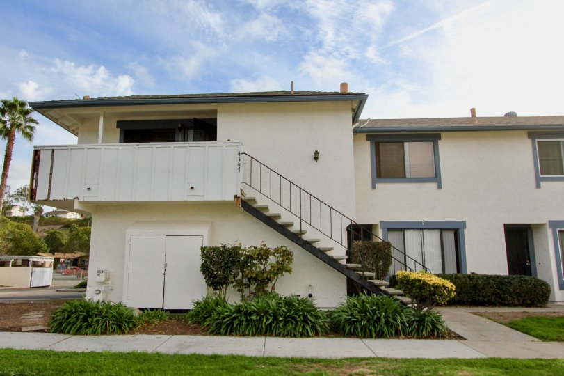 Two story house with stairs to second floor, sidewalk and grass/plants in front, located in the community of Seabreeze, in Oceanside, California.