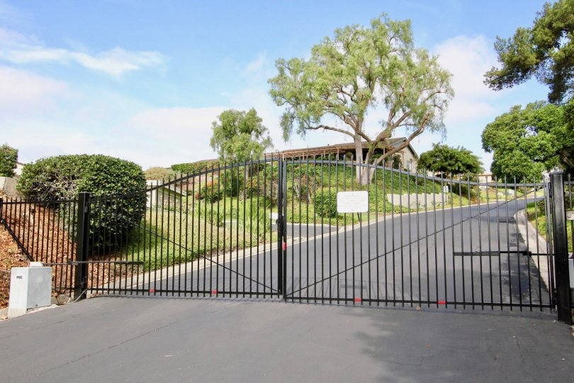 An entrance to a gated community with trees on either side of the road at Seawind