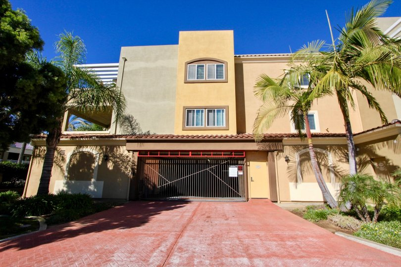 Private gates and palm tree lined drive of beautiful Summit Village.